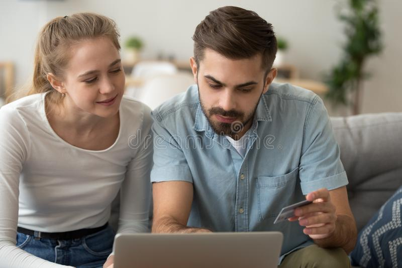 Young couple shopping online, paying for purchase by credit card. Young couple shopping online, paying for purchase, family sitting together on couch in living royalty free stock photo