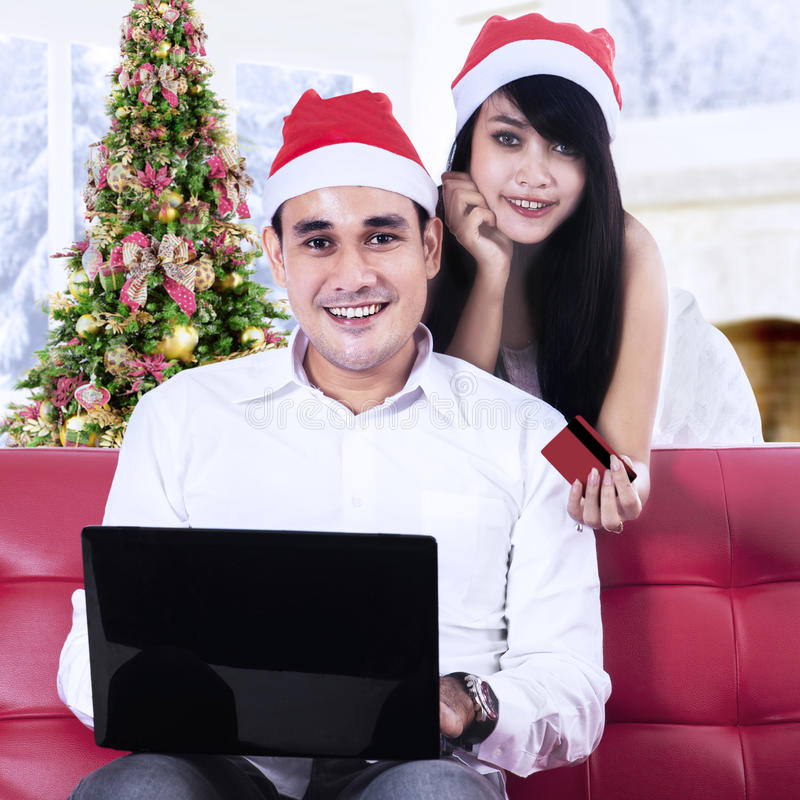 Young couple shopping online. Young couple in santa hats using credit card to shopping online stock image