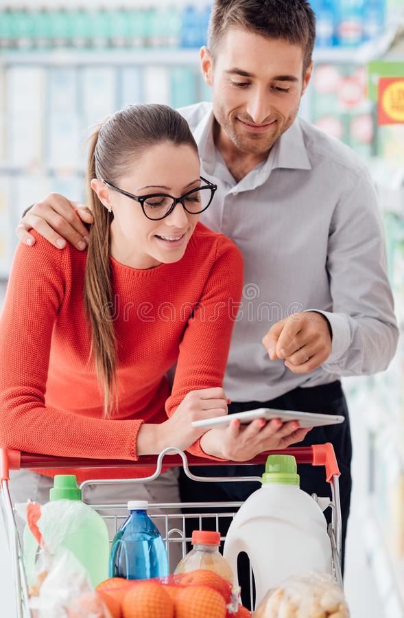 Young couple shopping with a tablet stock photography