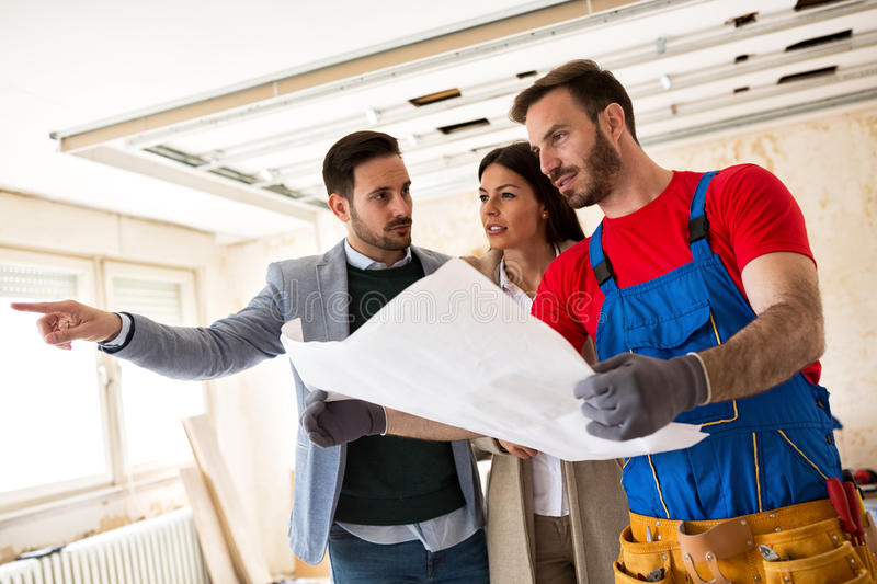 Young couple shows to builder handyman details about renovations royalty free stock image