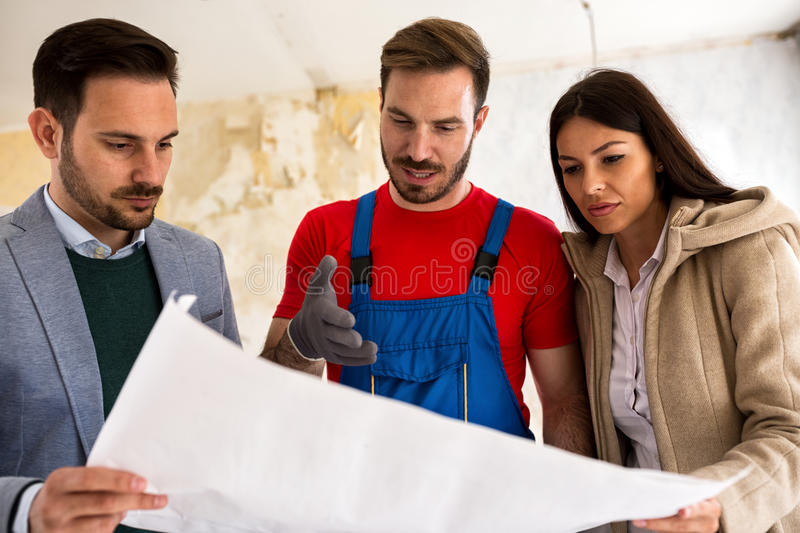 Young couple shows to builder handyman problem about renovations royalty free stock photography
