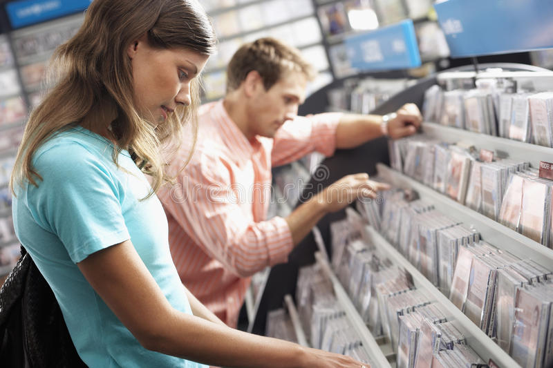 Young couple sifting through CDs in record shop, side view (tilt) stock photos