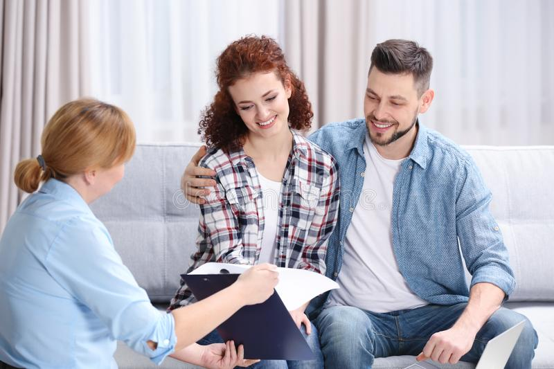 Young couple signing contract sitting on couch. At home royalty free stock photos