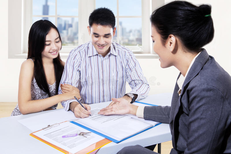 Young couple signing financial contract royalty free stock photography