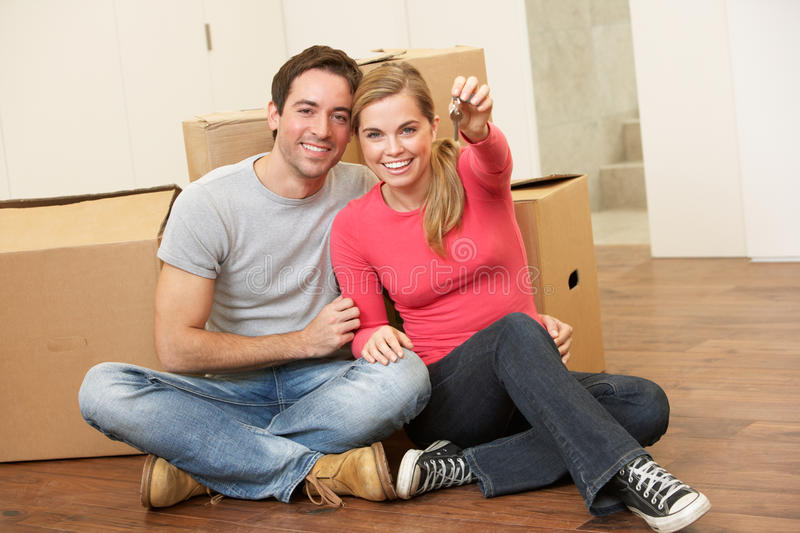 Download Young Couple Sit On The Floor Holding Key In Hand Stock Photo - Image: 18044516