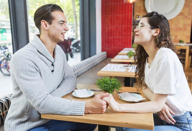 Beautiful young couple sitting at the table in cafe stock image