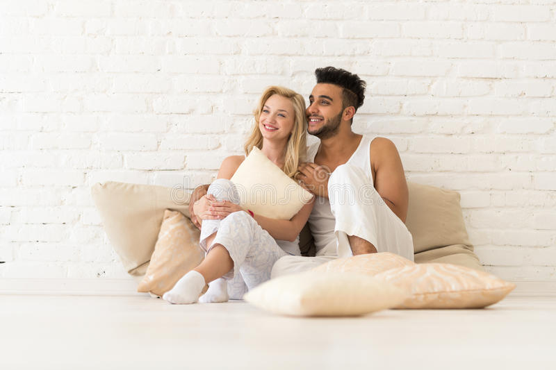 Young Couple Sit On Pillows, Happy Smile Hispanic Man And Woman Hug Lovers In Bedroom. Over White Brick Wall stock photography