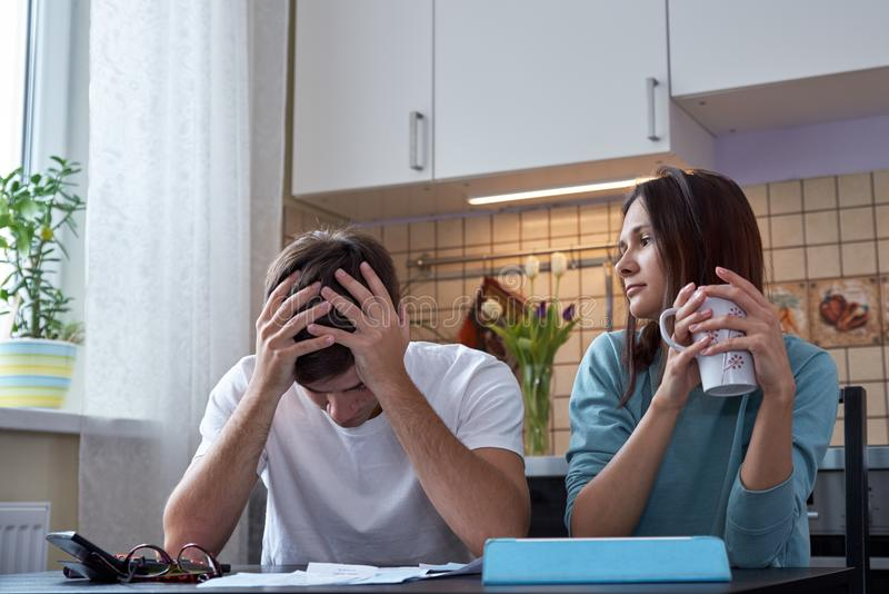 A young couple sits at a table in the kitchen and analyzes the family budget. The financial crisis in the family. stock photography