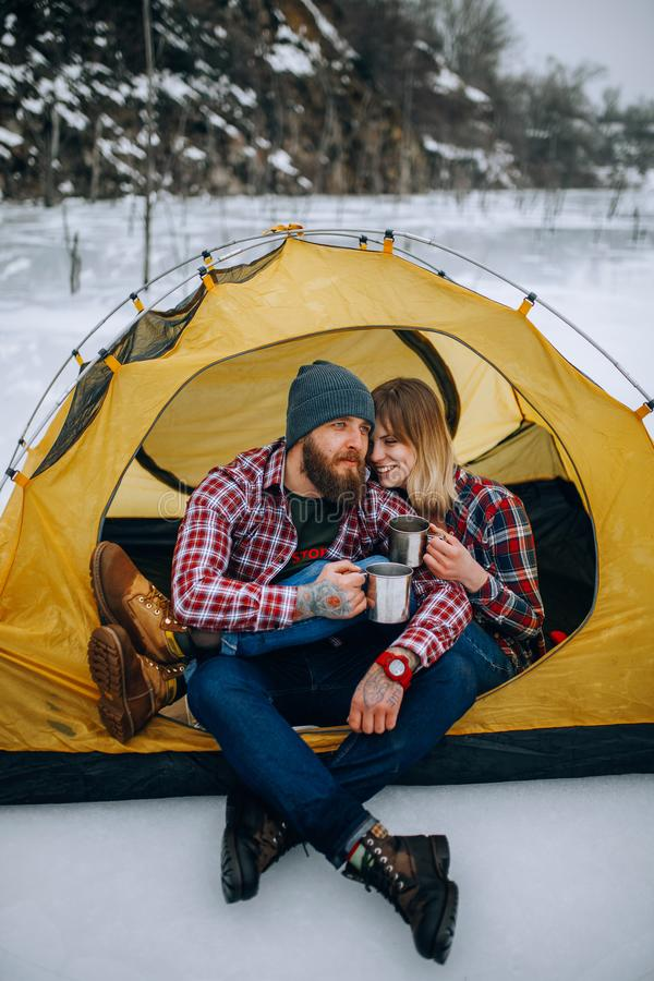 Young couple sits in tent and drinks hot tea during winter hike. stock images