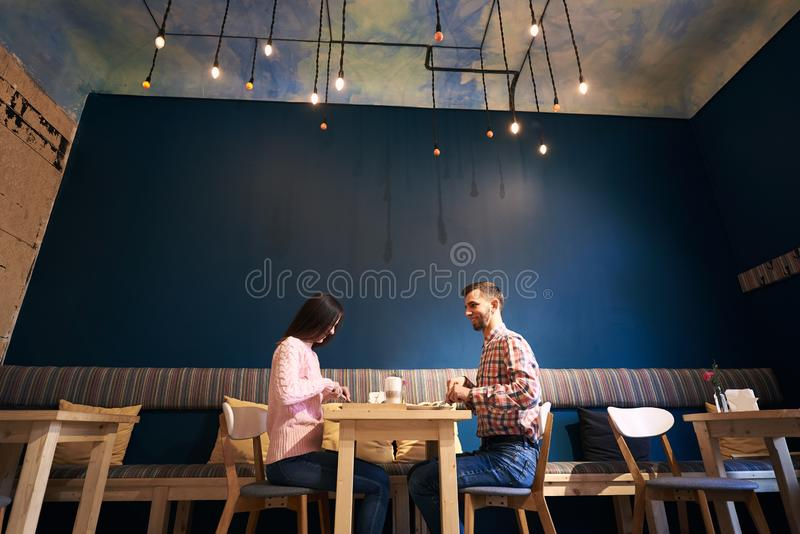 Two people in atmospheric cafe enjoying time spending with each other, having dinner, talking in cafe. Blue background. stock photos