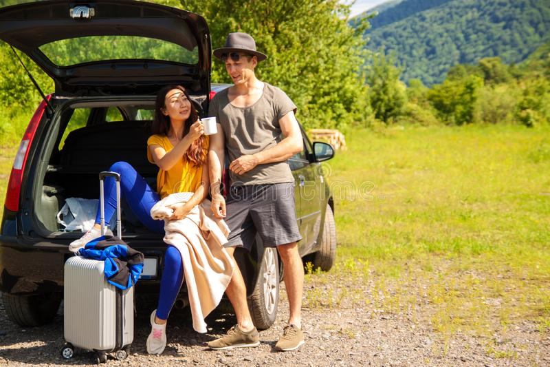 Beautiful young couple sitting in the trunk of a car and admire the beautiful scenery on the mountain. Young couple sitting on the back of a off road vehicle stock photo