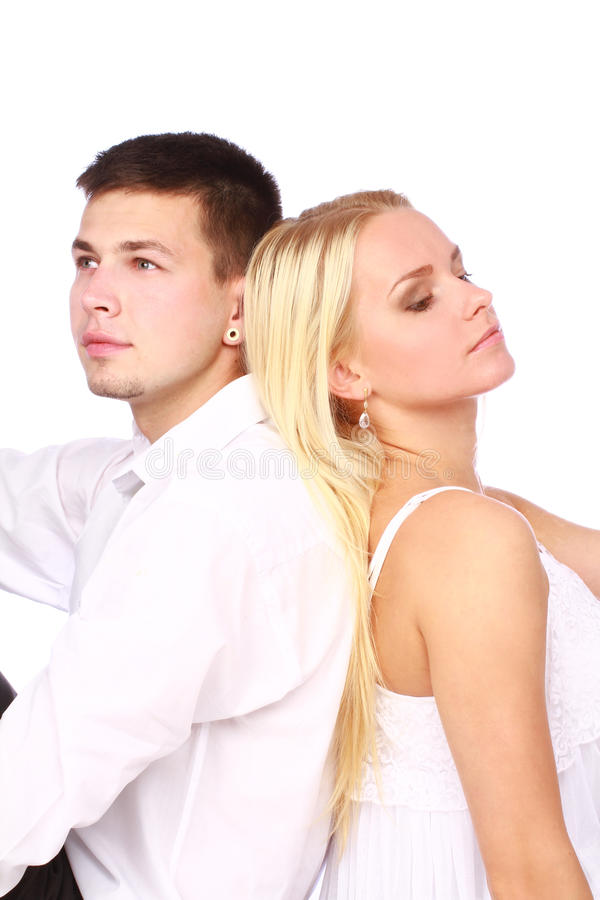 Young couple sitting back to back. On white background. Relationship problem concept royalty free stock images