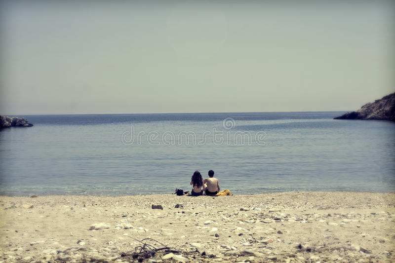 Download Young Couple Sitting On The Beach And Looking At Sea Stock Photo - Image: 38157408