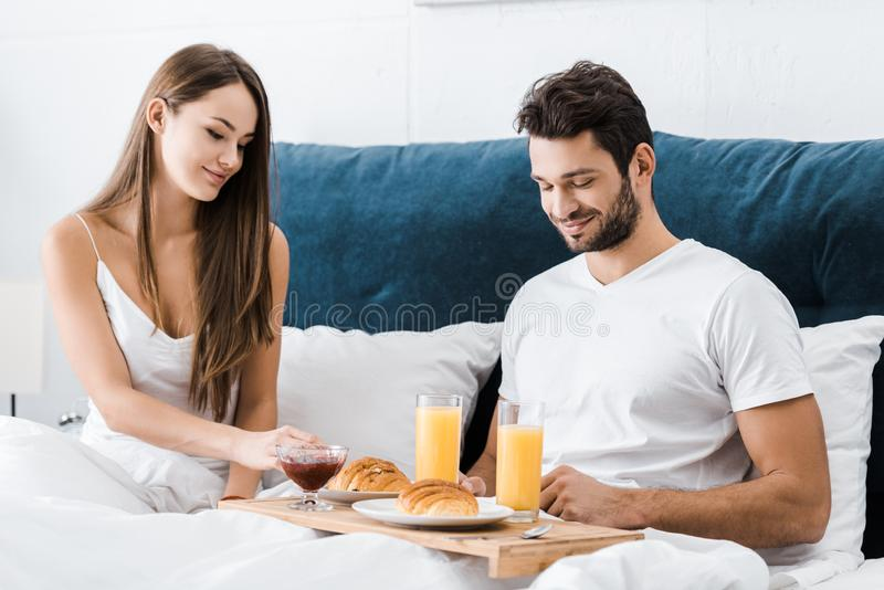 Young couple sitting in bed with breakfast stock image