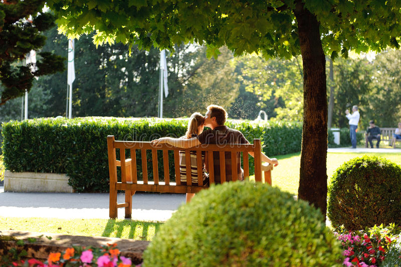 Young couple sitting on a bench in the park royalty free stock images