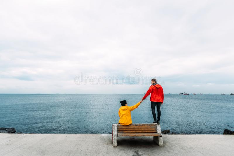 Young couple sitting on a bench by the sea. Man and woman traveling. People sit on a bench and look at the sea. Tourists by the stock photo
