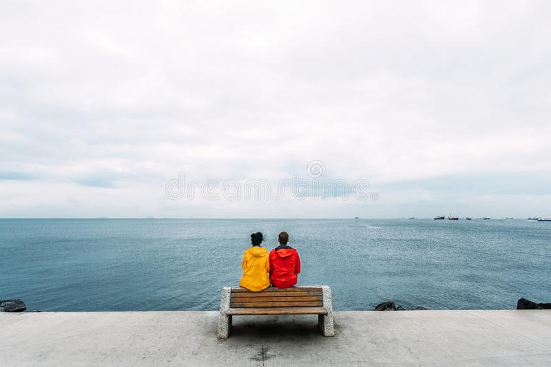 Young couple sitting on a bench by the sea. Man and woman traveling. People sit on a bench and look at the sea. Tourists by the royalty free stock images