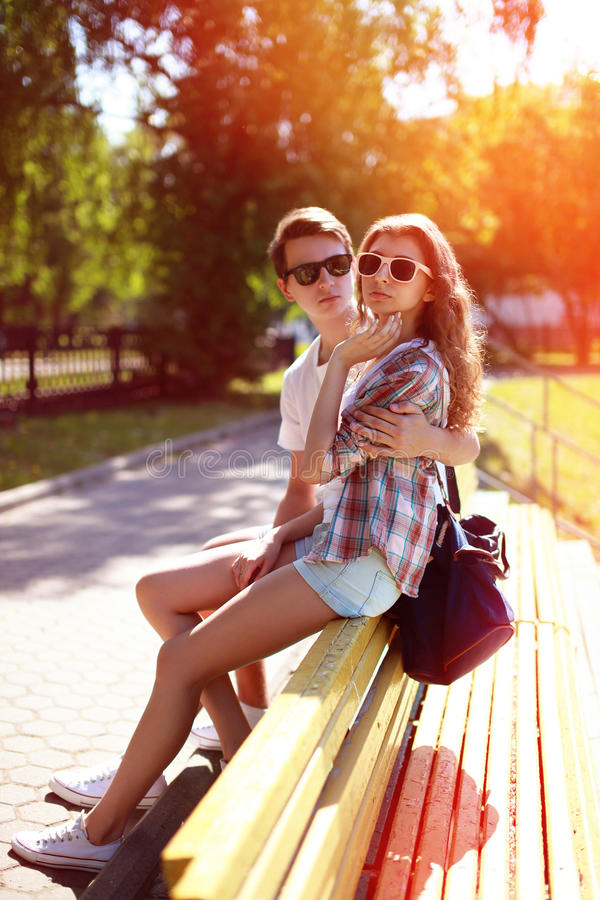 Young couple sitting in city park, summer sunny day royalty free stock photos