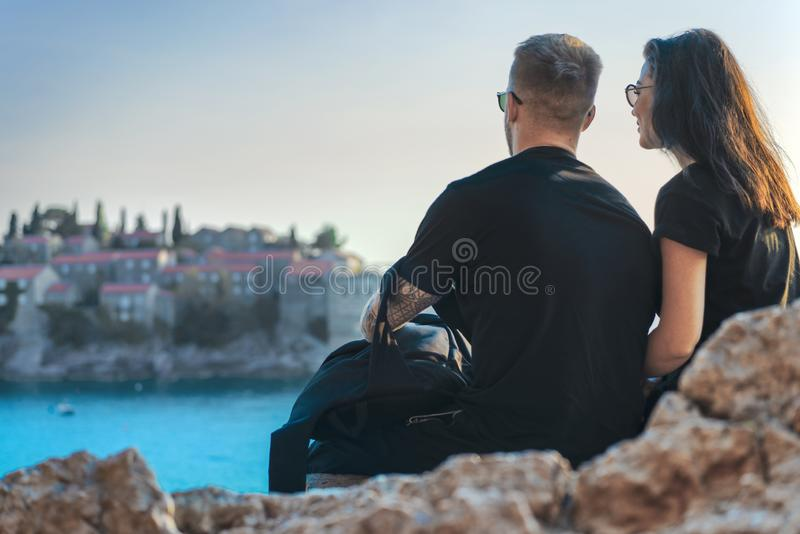 Young couple sitting on cliff above sea and looking at european town on island royalty free stock photo