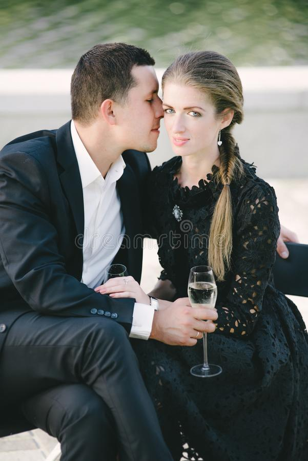 Young couple sitting close, man kissing her cheek royalty free stock photos