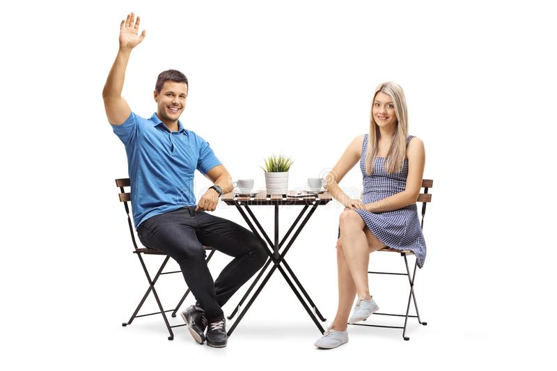 Young couple sitting at a coffee table, the guy waving stock images