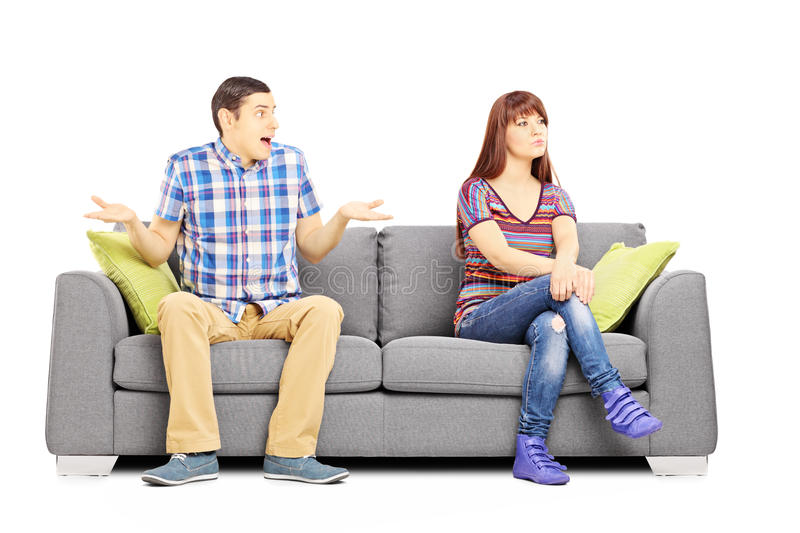 Young couple sitting on a couch during an argument. Isolated on white background royalty free stock image