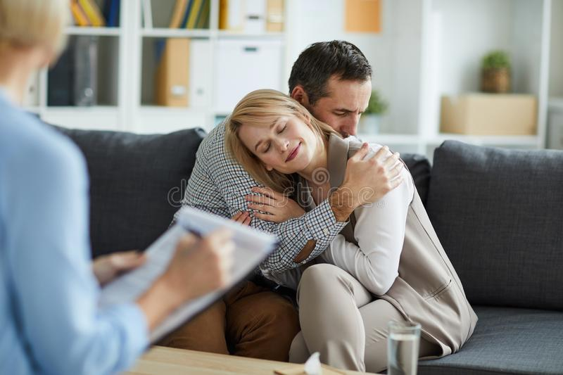 Couple in embrace. Young couple sitting on couch in embrace after consulting with counselor and solving their problem royalty free stock image