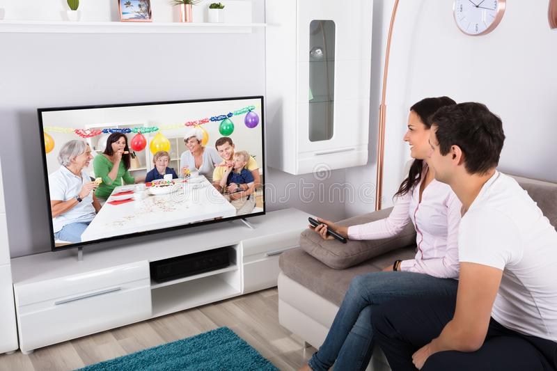 Couple Watching Birthday Celebration On Television stock photos