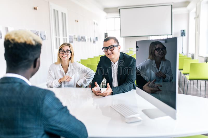 Young couple sitting at a desk in the office of their african agent or adviser discussing an investment presentation on a document. Young couple sitting at a royalty free stock images