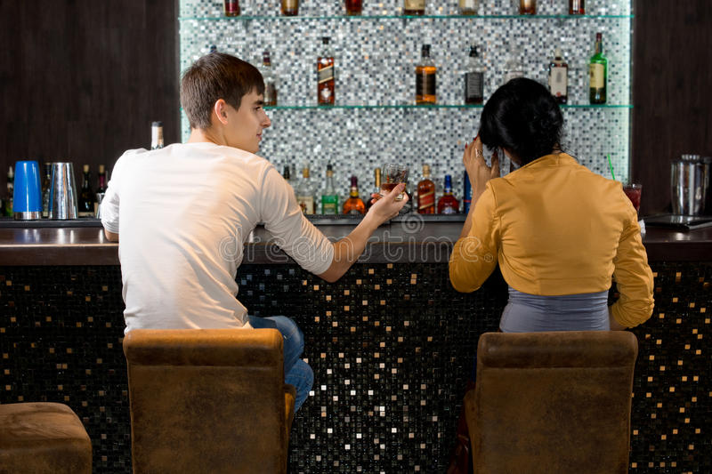 Young couple sitting drinking at the bar royalty free stock photo
