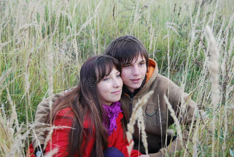 Young couple sitting in the field. stock image