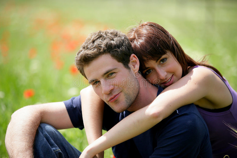 Young couple sitting in a field royalty free stock photography