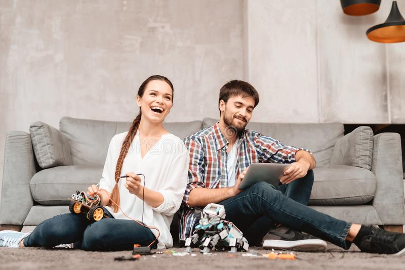 A young couple is sitting on the floor in the living room. They collect robots. stock photo