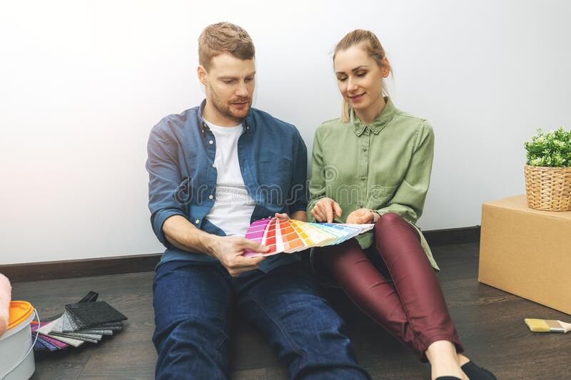 Young couple sitting on the floor in the room and choosing paint color from samples for new interior stock photography