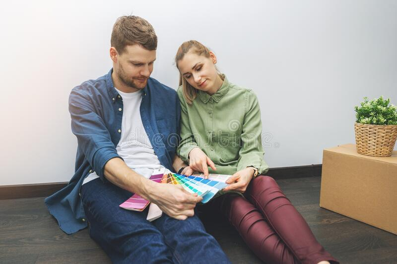 Young couple sitting on the floor in the room and choosing paint color from swatch stock image