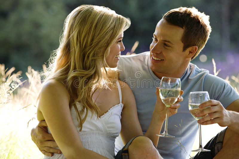 A young couple sitting on the grass, drinking wine stock images