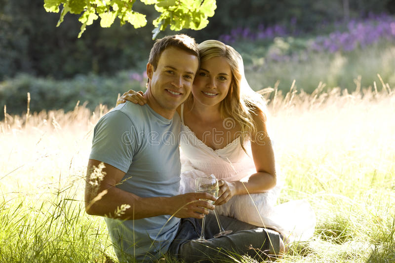 A young couple sitting on the grass, drinking wine royalty free stock photography