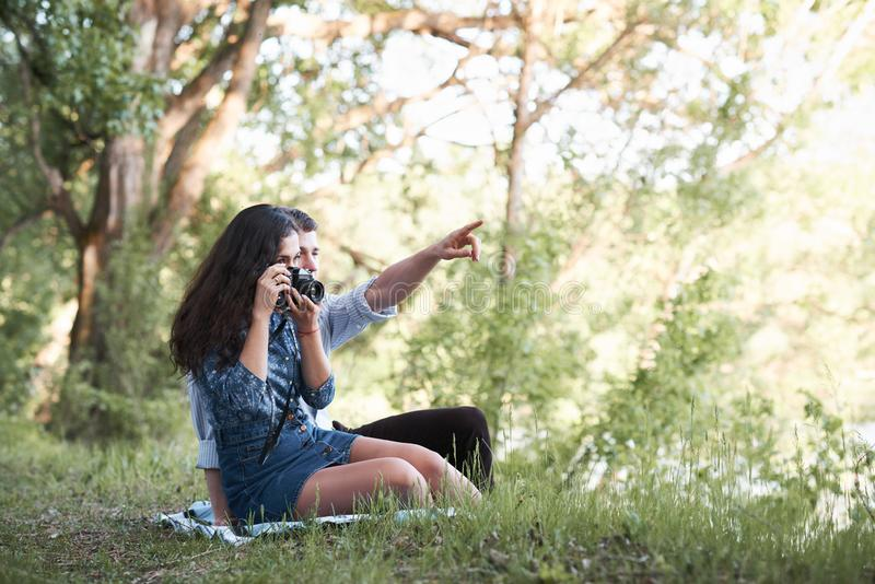 Young couple sitting on the grass in the forest, taking photos and looking on sunset, summer nature, bright sunlight, shadows and. Green leaves, romantic royalty free stock photo