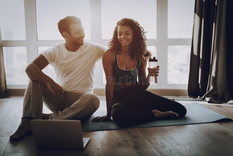 Young Couple Sitting On Gym Carpet With Laptop. Afro American Couple Sitting On Gym Carpet With Laptop. Healthy Lifestyle. Shape Sportswear. Attractive Athletes royalty free stock photography