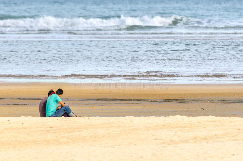Young couple sitting and having fun. On beach stock images