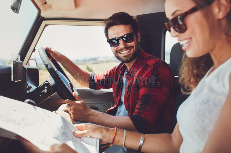 Young couple sitting inside their car with map stock photo