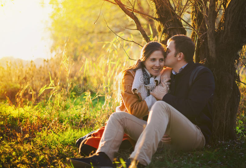 Young couple sitting and kissing near the tree. In the forest royalty free stock photography