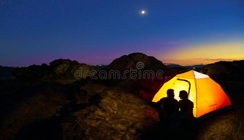 Young Couple Sitting near Illuminated Tent and Looking at Each Other at Beautirul Evening in the Mountains royalty free stock photos