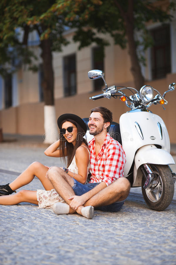 Young couple sitting near white retro scooter royalty free stock photography