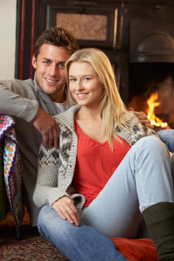 Young couple sitting by open fire. Smiling stock image