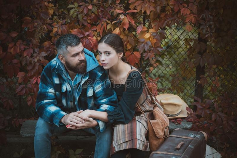 Young couple sitting outdoors at the park on beautiful autumn day. Lifestyle, happy couple of two play on a sunny day in royalty free stock image