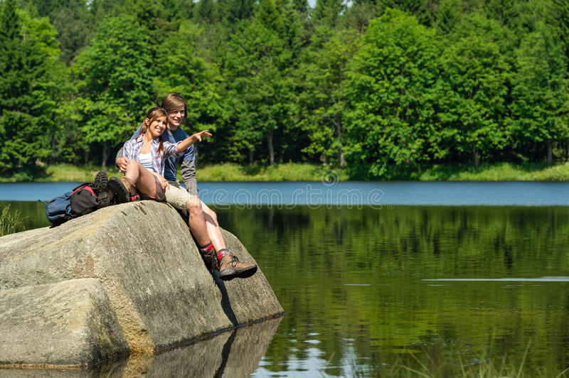 Young couple sitting on rock by the lake royalty free stock images
