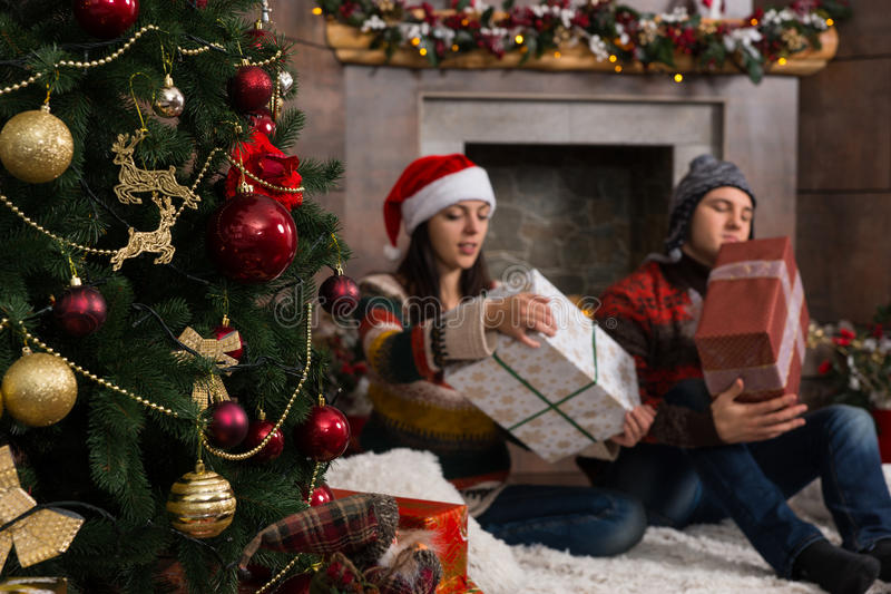 Young couple sitting on a rug in front of the decorated fireplace and Christmas tree unwrapping their Christmas gifts royalty free stock images