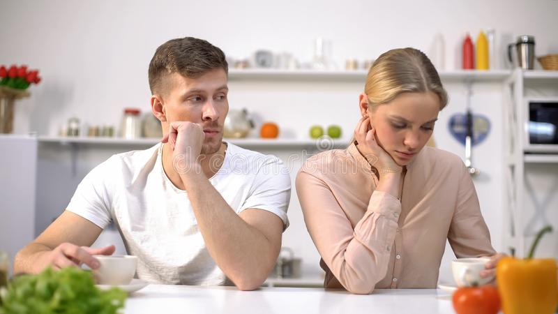Young couple sitting silently in kitchen after argument, crisis in relationship royalty free stock image