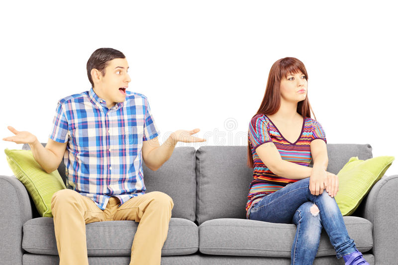 Young couple sitting on a sofa during an argument. Isolated on white background royalty free stock photo
